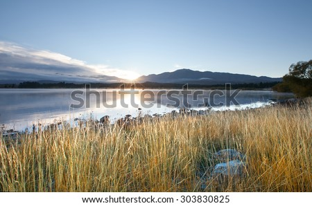 Morning mist moving over Lake Tekapo, South Island, New Zealand. Lake Tekapo is the second-largest of three roughly parallel lakes in the South Island of New Zealand.  - stock photo