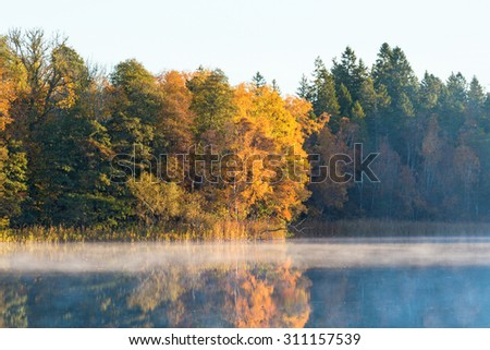 Morning mist on the lake with forest in autumn colors - stock photo