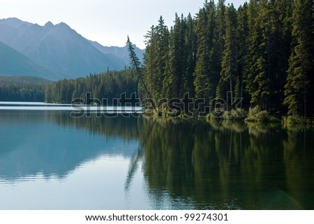Morning on lake in Canadian Rockies with reflection - stock photo