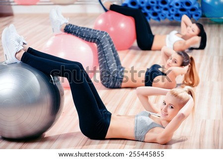 Morning pilates. Three beautiful young women in sports clothing exercising together on fit balls at the gym and smiling  - stock photo