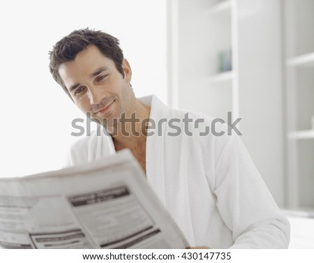 Morning portrait of handsome guy reading newspaper