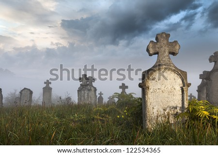 Morning quarters of some very old tombstones in a very old abandoned cemetery in Hungary. It was a stormy day - stock photo