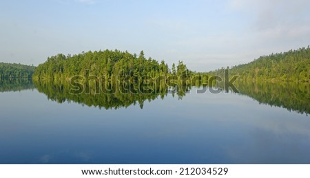 Morning Reflections on Emerald lake in the Quetico - stock photo