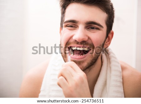 Morning routine of washing the teeth. Handsome young man is brushing teeth with toothbrush and smiling. - stock photo