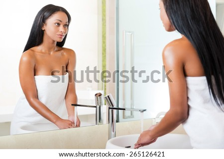 Morning routine. Rear view of beautiful young African woman washing hands in bathroom and looking at the mirror  - stock photo