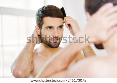 Morning routine. Rear view of handsome young beard man combing his hair while standing against a mirror  - stock photo