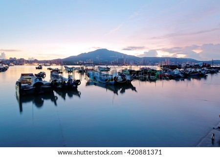 Morning scenery of Tamsui River at sunrise in Taipei Taiwan, with a peaceful view of ferry boats parking on smooth water by the riverside & Datun Mountain under beautiful dawning sky in background - stock photo