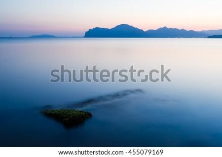 Morning sea landscape. Mountain on the horizon. Water blurred long exposure camera. Crimea, Ukraine, Europe - stock photo