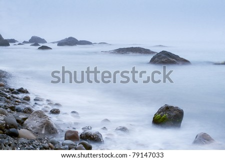 Morning sea shore with surf and rocks
