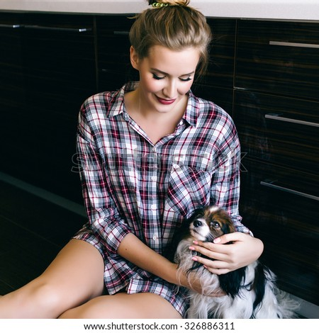 Morning sensual portrait of blonde pretty woman playing with her small dog at the kitchen,  sitting on the floor, wearing plaid shirt, cozy atmosphere, vintage film soft colors. - stock photo