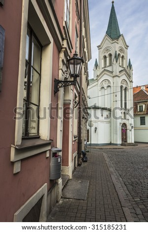 Morning street in medieval town of old Riga city, Latvia. Walking through medieval streets of old Riga, tourists can find unique architectural ensembles and ancient houses - stock photo