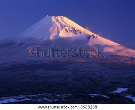 Morning sun illuminating the peak of Mount Fuji on a clear Winter's day - stock photo