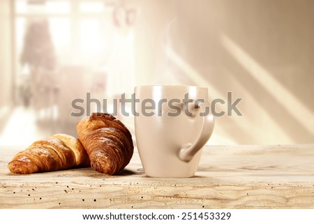 morning sun in window and coffee mug with croissants  - stock photo
