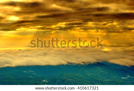 Morning sun shining through the clouds over the mountain