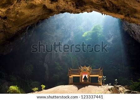 Morning sunbeam on golden buddhist pavilion in wild cave, Sam Roi Yot, Thailand - stock photo