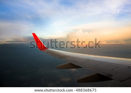 Morning sunrise with Wing of an airplane flying above the ocean. The view from an airplane window. Photo applied to tourism operators. picture for add text message or frame website. Traveling concept