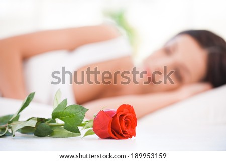 Morning surprise. Side view of beautiful young woman lying in bed with red  - stock photo