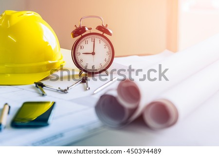 Morning time it's nine o'clock already, Retro clock showing 9:00 am on the desk of engineer designer and architect in an office with equipment and drawing paper for working plan. - stock photo