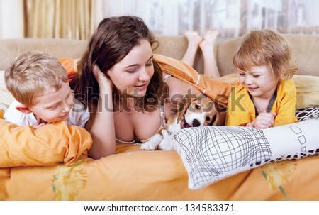 Morning time scene. Children  with beagle puppy in the bed - stock photo