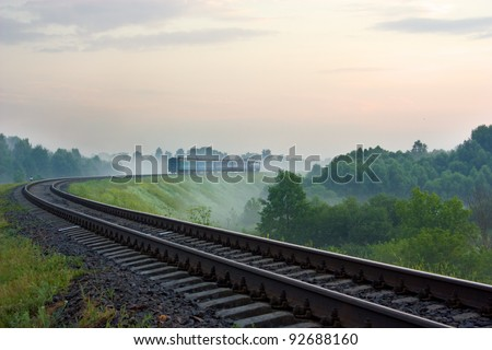 morning train passing in the fog - stock photo