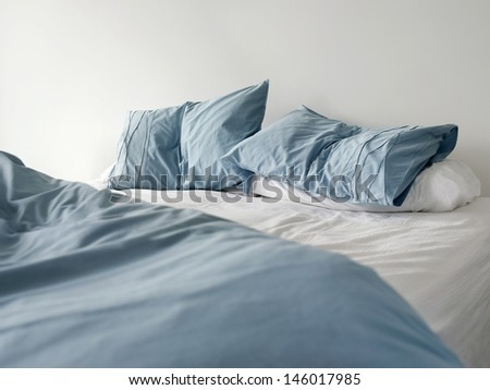 Morning view of an unmade bed with crumpled blue bed linens and no people - stock photo