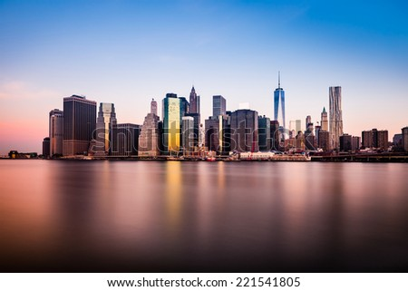 Morning view of lower Manhattan silhouette reflecting in the clear waters of East River - stock photo