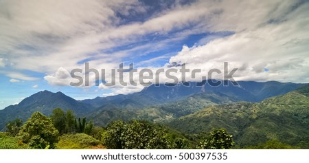 Morning view of Mount Kinabalu with clear blue sky covered by thick cloud.