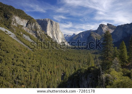 Morning view of Yosemite Valley under beautiful skies from Tunnel View viewpoint with Half Dome in the distance.