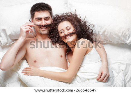 Morning with good mood. Overhead of happy beautiful young couple lying on the bed having fun together, laughing and hugging, Top view. - stock photo
