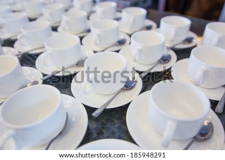 Morning workplace: cup of coffee and business objects on the table in seminar - stock photo