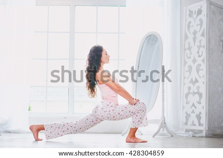 Morning yoga. Attractive young woman stretching on floor in her apartment. - stock photo