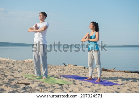 Morning Yoga Meditation at the Beach by young couple - stock photo