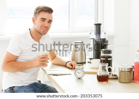 Morning. Young man by the table - stock photo