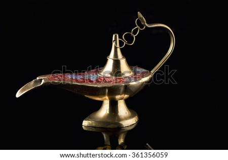 Moroccan brass oil lamp on black mirror background with reflection