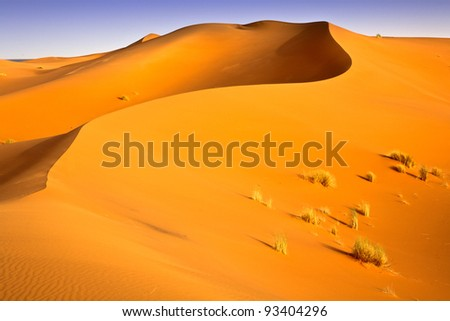 Moroccan desert dunes landscape with blue sky. - stock photo