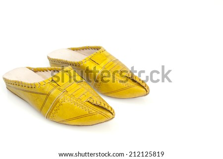 Moroccan girl's handmade yellow slippers. A tiny pair of delicate, intricately detailed yellow slippers from Morocco, isolated on white. Picture from the side, higher up - stock photo