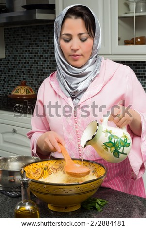 Moroccan immigrant woman in modern European kitchen preparing couscous for Ramadan nights - stock photo
