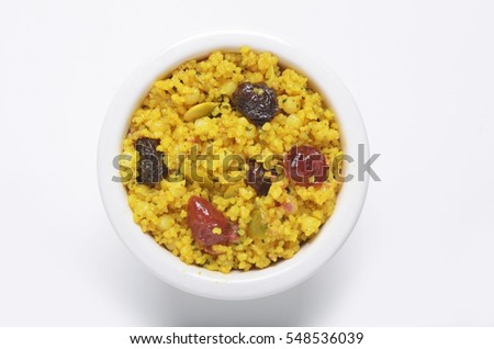 Moroccan style couscous with raisins cranberries and pumpkin seeds in a white ceramic bowl shot from directly above on white background