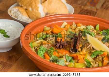 Moroccan tagine dish with chick peas, lamb, carrots, celery, lemon, onion, cinnamon, star anise - stock photo