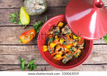 Moroccan Tagine with lamb, pumpkin and red pepper on a wooden table. Selective focus