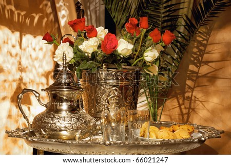 Moroccan tea set with pasteries and white and red roses. Traditional arabic and moroccan tea culture.