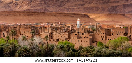 Moroccan village with mud brick houses in mid Atlas mountains. - stock photo