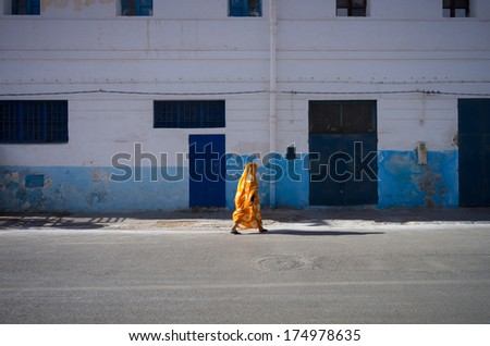 Moroccan woman dressed in traditional clothing crossing the street