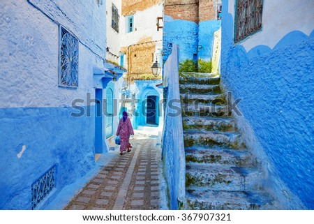 Moroccan woman in traditional clothes (jellaba) walking on a street in Medina of Chefchaouen, Morocco, small town in northwest Morocco known for its blue buildings - stock photo