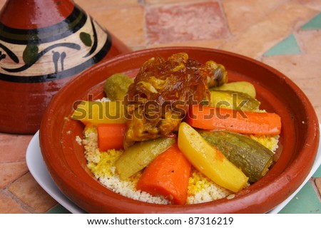 Morocco Couscous dish - Tajine roasted chicken leg with caramelized onions saffron and  cooked fresh vegetables on a bed of couscous - stock photo