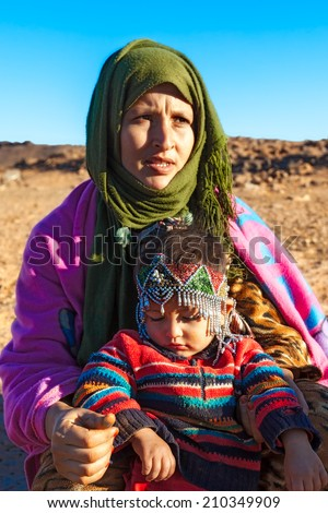 MOROCCO-DEC 28, 2012: An unidentified nomadic mother and child in the Sahara desert Maider region, where Berbers camp to graze their herds. The child is wearing a traditional beaded headpiece.     - stock photo