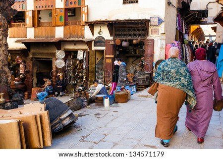 MOROCCO-JAN 3: Shoppers in the historic medina in Fes, Morocco on Jan. 3, 2013. The Unesco World Heritage site attracts both locals and tourists to the alleyways full of shops. - stock photo