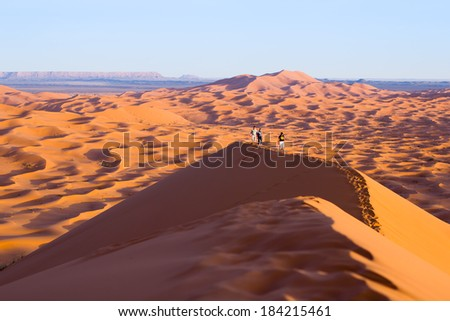 MOROCCO - JANUARY 10, 2014: Travelers climb a large dune in the Sahara. - stock photo