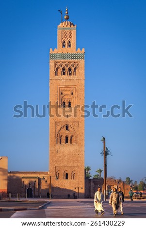 MOROCCO, MARRAKESH - DECEMBER 28: Moroccan people walking in front of the minaret of the Koutoubia Mosque on December 28, 2014 in Marrakesh, Morocco - stock photo