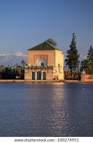 Morocco Marrakesh Menara Pavilion and Gardens reflected on lake in late afternoon sunshine with snow covered peaks of the Atlas Mountains in the background - stock photo